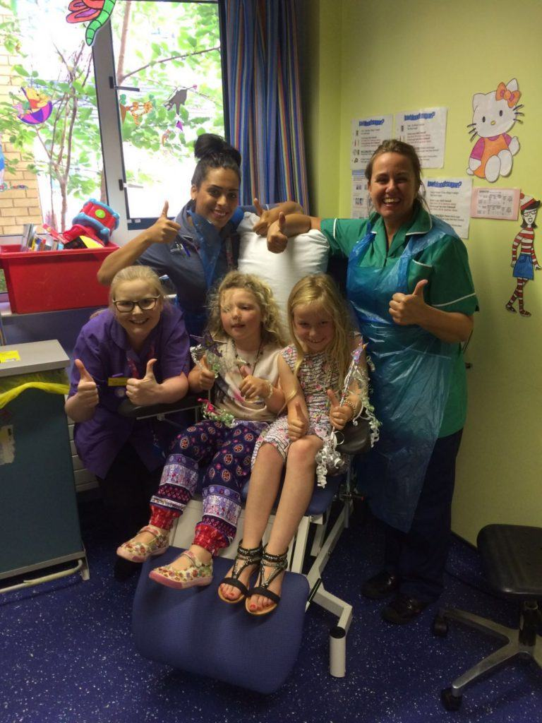 Evelyn 5 with her sister Abigail 7 and nurses after her regular blood test.